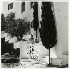 Salvador Dalí standing on the stairs of his house in Portlligat. This is an ancient black and white image, and the artist has a catalan cap on his head.