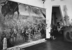 Black and white photograph of one of Salvador Dalí's House-Museum rooms in Portlligat. We see the artist at the entrance of the room, and a large painting at his right