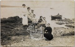 Ancient black and white photograph. Dalí's family in a cove, and a fisherman's boat on their back.