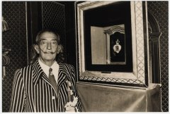 Black and white photography of Salvador Dali, along with one of his jewelry collection's work.