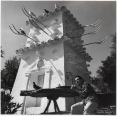 Picture of Salvador Dali under the tower of the House-Museum of Portlligat. It is a black and white picture.
