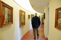 A man walks along a corridor of an exhibition of paintings of Antoni Pitxot i Soler.