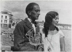 Black and white photograph of Anna Maria and Salvador Dalí on a cove, with some boats behind them.