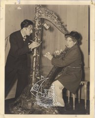 Salvador Dalí and Harpo Marx playing the harp at the artist's workshop.