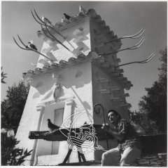 Ancient black and white photograph of Salvador Dalí at the base of the House-Museum's tower at Portlligat
