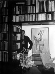 Dalí, laying his back on a shelve full of books, and a picture of the artist at the background of the photograph.
