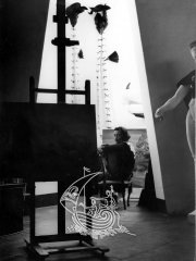 Black and white photograph. In the forefront of the image we can see a painting of Salvador Dalí in a room of his house in Portlligat. At the end of the image we can see the artist.