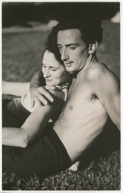 A photograph of Salvador Dalí and Gala, lying on the grass in an affectionate attitude