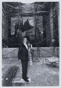 Picture of Salvador Dalí at the courtyard under construction of the Theatre-Museum in Figueres. There are some of the artist's works behind his figure