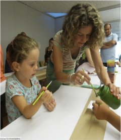 A woman teaches a little girl how to use a brush to paint.