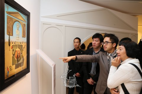 Adrian Cheng, Founder and Honorary President of K11 Art Foundation showing a piece of the exhibition