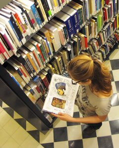 A girl at the Centre for Dalinian Studies looks at an open book that has in her hands.